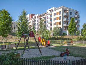 Dětské hřiště a v pozadí bytový dům Hortenzie a Gladiola